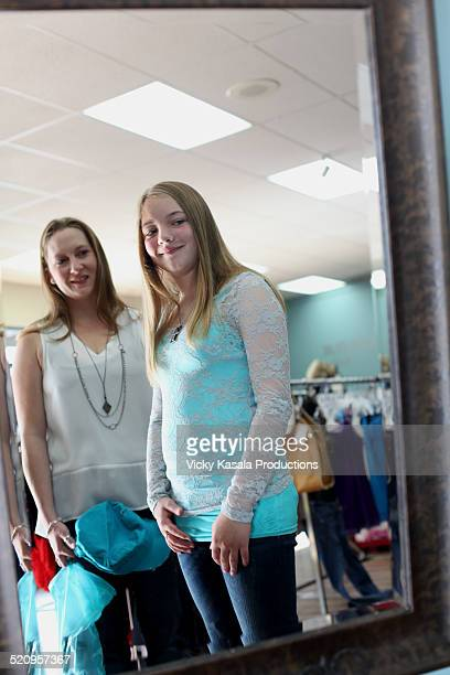 Mother and daugher clothes shopping.