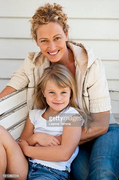 Mother and daugher sitting on bench outside