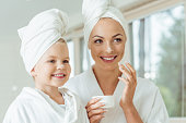 beautiful happy mother and daughter in bathrobes and towels applying face cream together