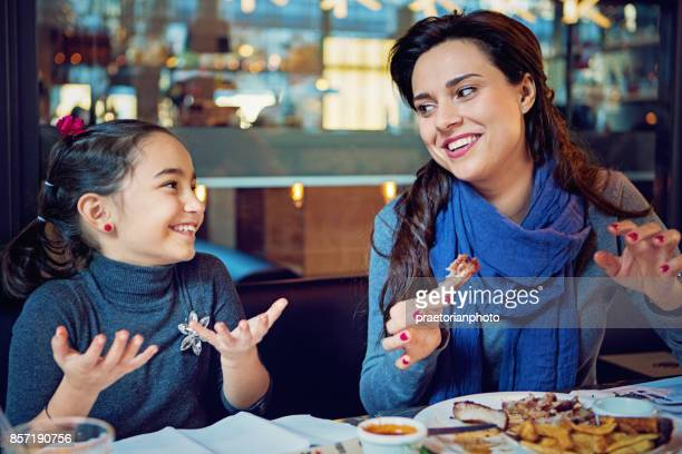 Mother and daughter are eating pork ribs in the restaurant with hands