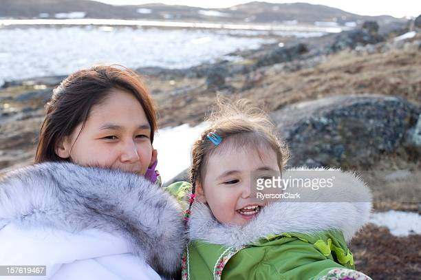 A mother and daughter are on an island smiling and pointing