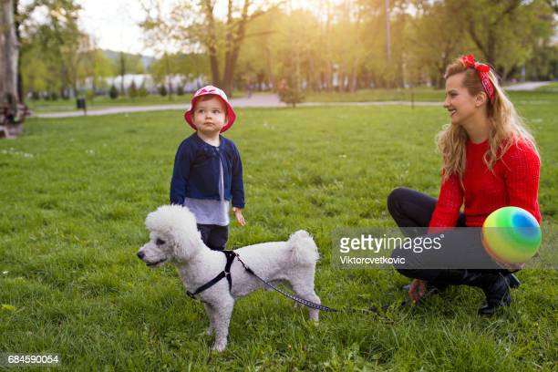 Mother and daughter are playing in park with dog