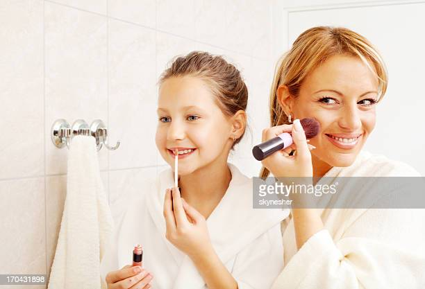 Mother and daughter are putting on make up.