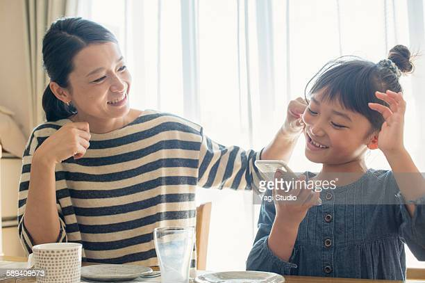 Mother and daughter are relaxing to sit on table