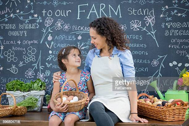 A mother and daughter are selling thier produce at