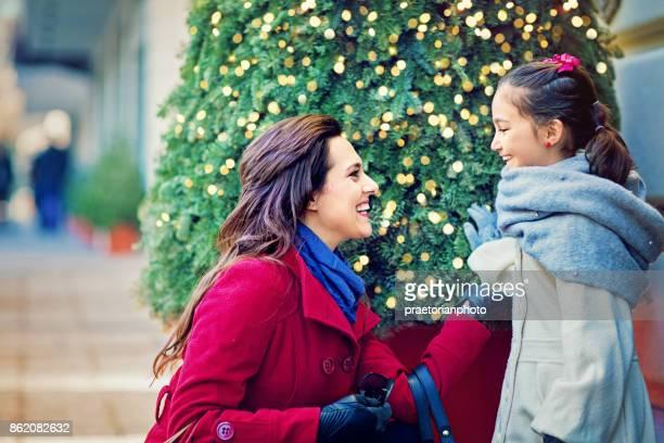 母と娘は、クリスマス ツリーの前に立っています。