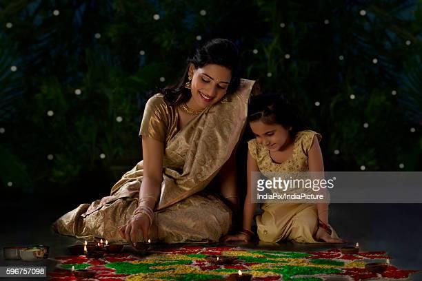 Mother and daughter arranging diyas