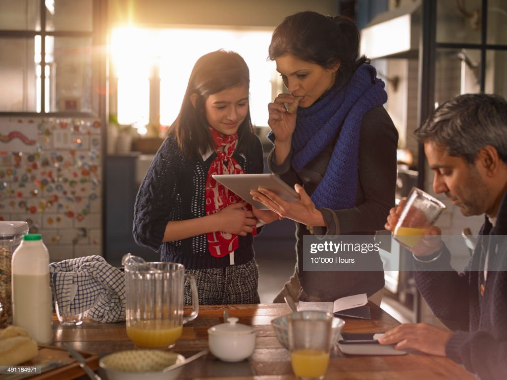 Mother and daughter at breakfast looking at ipad : Stock Photo