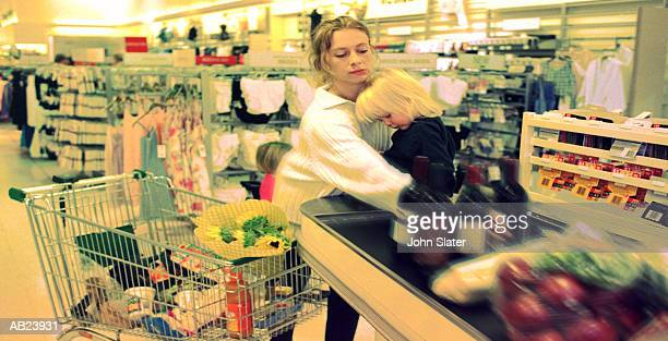 Mother and daughter (21-24 months) at checkout in supermarket