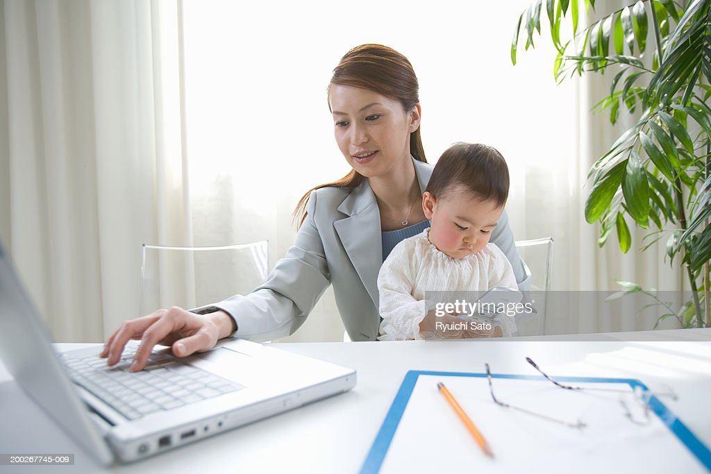 Mother and daughter (6-9 months) at desk, woman using laptop computer : Stock Photo