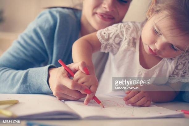 Mother and daughter at home. Mother teaching her daughter to drawing and writing.