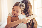 Beautiful young woman and her charming little daughter are hugging and smiling