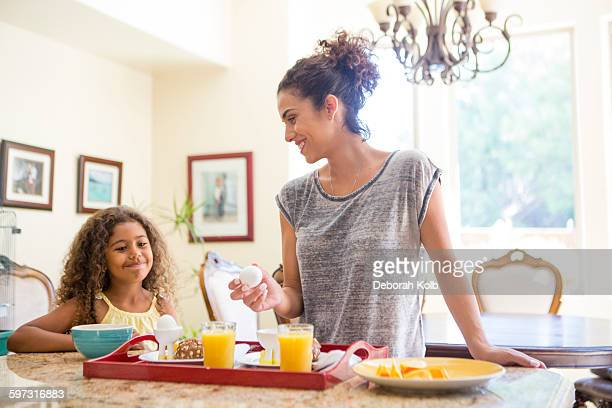 Mother and daughter at home preparing breakfast tray smiling