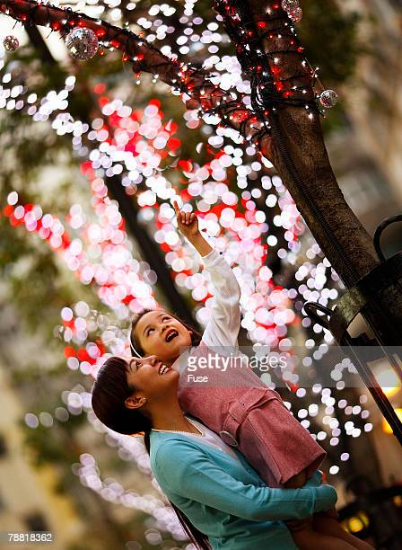 Mother and Daughter at Illuminated Tree