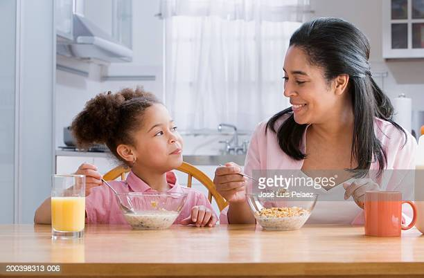 Mother and daughter (4-6) at table eating cereal