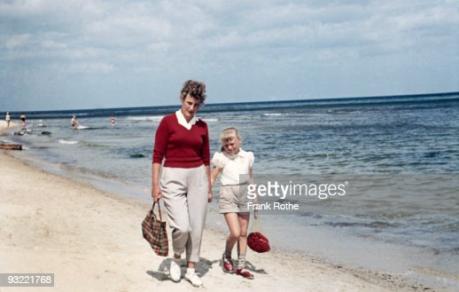 mother and daughter at the beach walking : Stock Photo