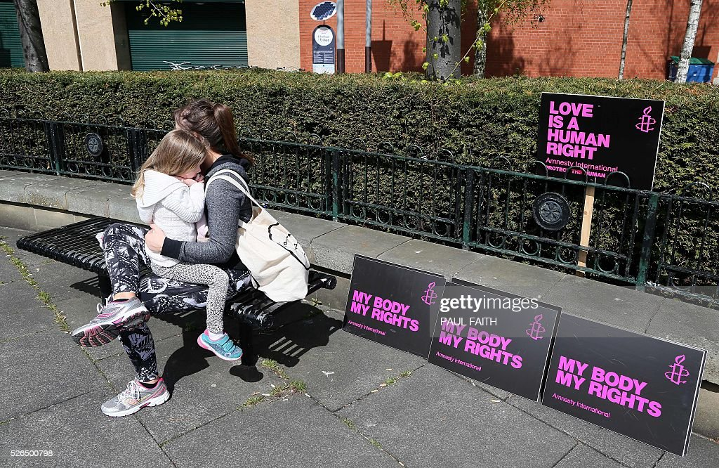 A mother and daughter await the start of a pro-choice demonstration through Belfast city centre on April 30, 2016. Abortion prosecutions in Northern Ireland have forced the issue to centre of the campaign ahead of next week's regional elections, with unprecedented political support for an end to the current ban. Northern Ireland currently bans abortion in all cases except when the life of the mother is in danger / AFP / PAUL