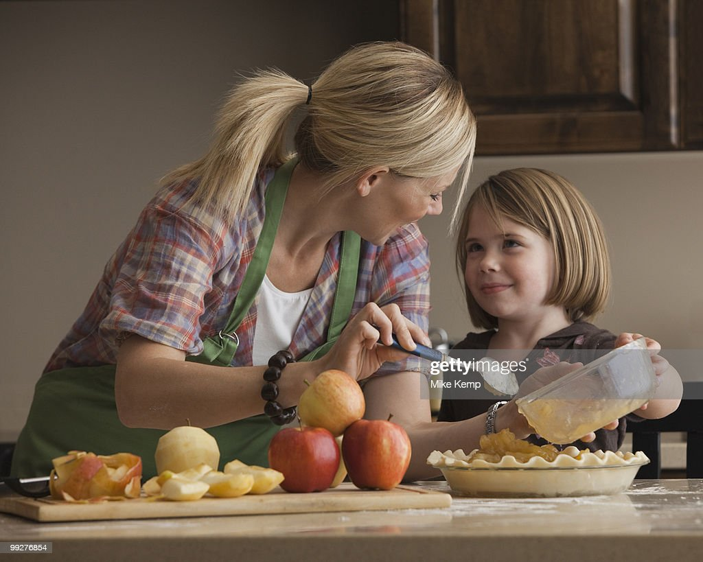 Mother and daughter baking apple pie