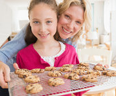 Mother and daughter (8-9 years) baking cookies