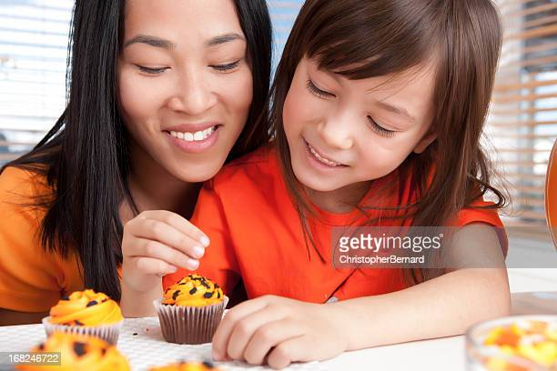 Mother and daughter baking halloween cupcakes