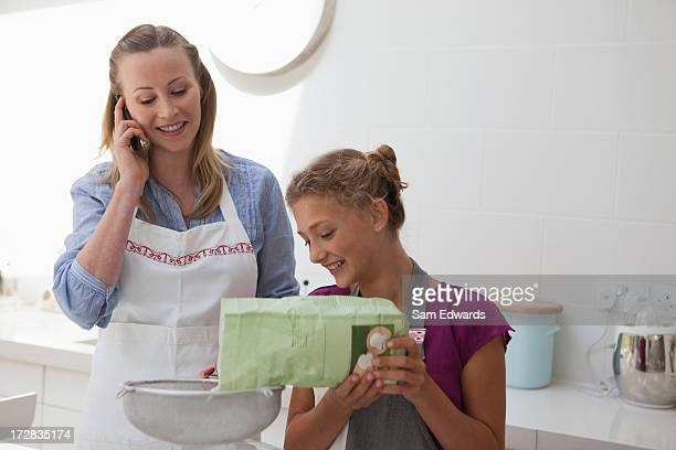 Mother and daughter baking in kitchen talking With cell phone
