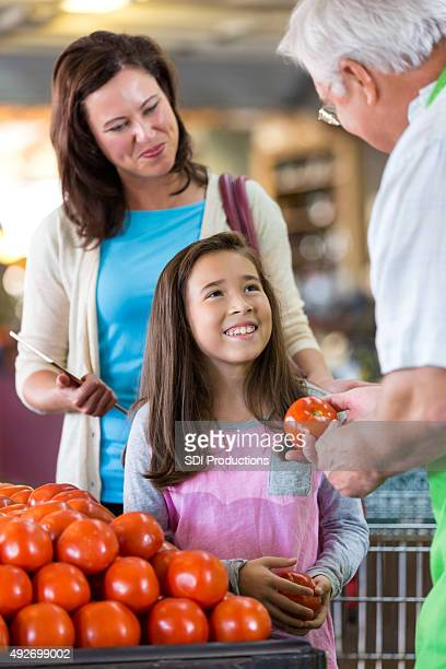 Mother and daughter being helped by grocery store owner