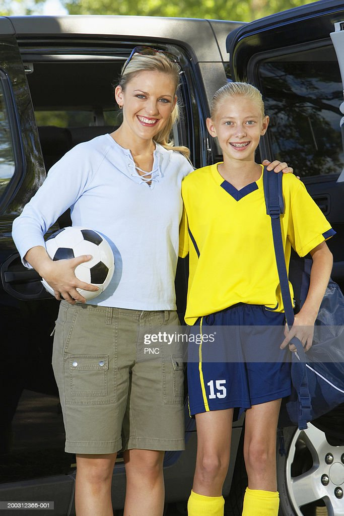 Mother and daughter (11-13) beside SUV, girl wearing soccer uniform