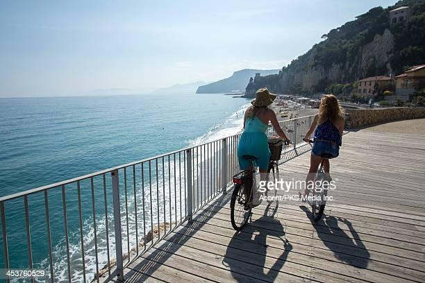 Mother and daughter biking along boardwalk