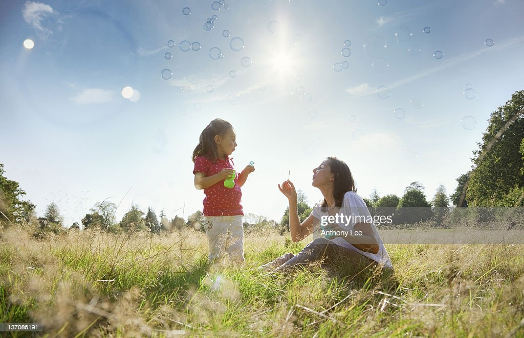 Mother and daughter blowing bubbles in sunny rural field : Stock Photo