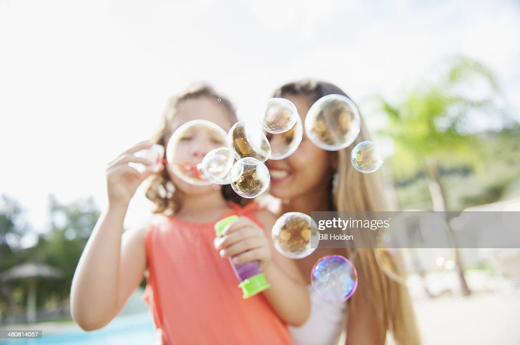 Mother and daughter blowing bubbles
