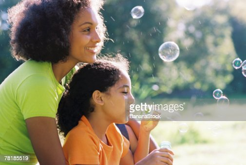 Mother and daughter blowing bubbles : Stock-Foto
