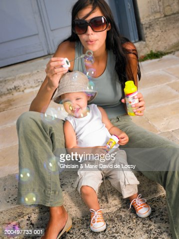 Mother and daughter (18-21 months) blowing bubbles with bubble wand : Photo