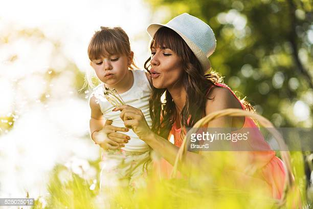 Mother and daughter blowing dandelion in the park.