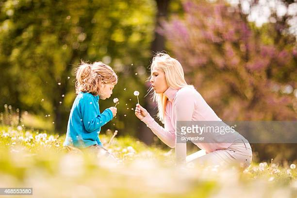 Mother and daughter blowing dandelions in the park.