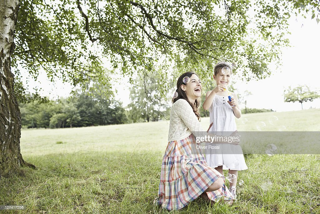 mother and daughter blowing soap bubbles : Stock Photo