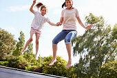 Mother And Daughter Bouncing On Trampoline Together Smiling