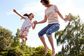 Mother And Daughter Bouncing On Trampoline Together Laughing