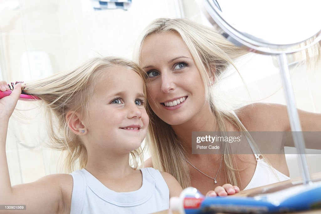 mother and daughter brushing hair in bathroom : Stock Photo