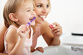 Mother And Daughter Brushing Teeth Together Over Sink