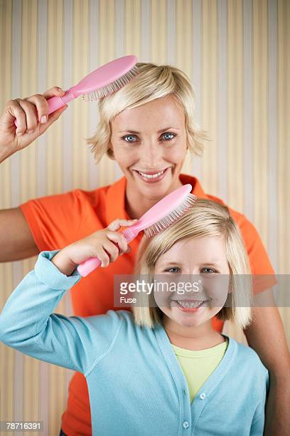 Mother and Daughter Brushing Their Hair