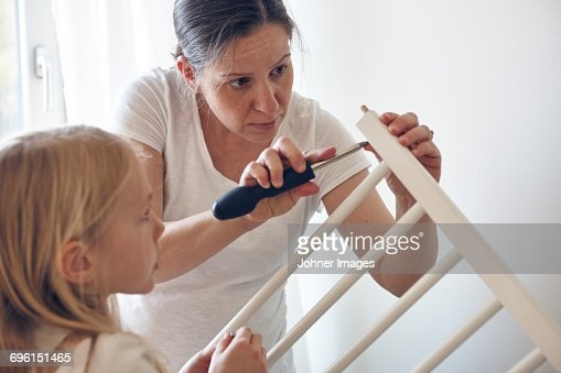 Mother and daughter building cot
