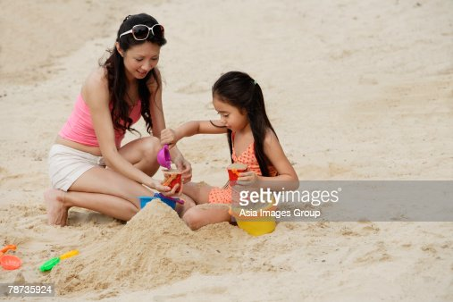 Mother and daughter building sand castle on beach : Stock Photo
