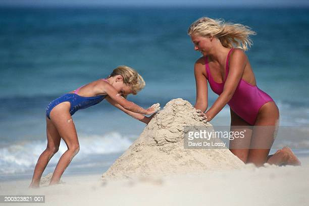 Mother and daughter (4-5) building sandcastle