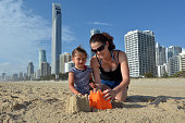 Young mother and daughter builds sand castle on Surfers Paradise main beach in Gold Coast Queensland, Australia.