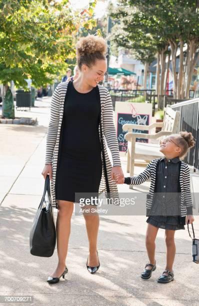 Mother and daughter businesswomen walking on sidewalk