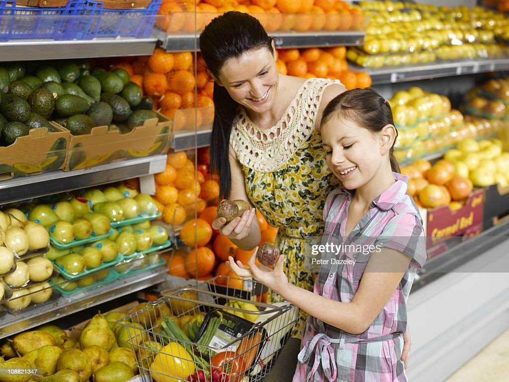 Mother and daughter buying fruit in supermarket : Stock Photo