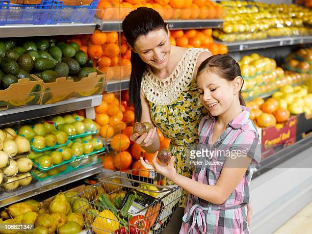 Mother and daughter buying fruit in supermarket