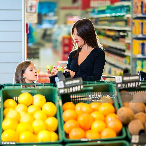 Mother and daughter buying fruit together