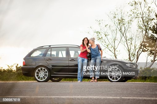 Mother and daughter by car on roadside