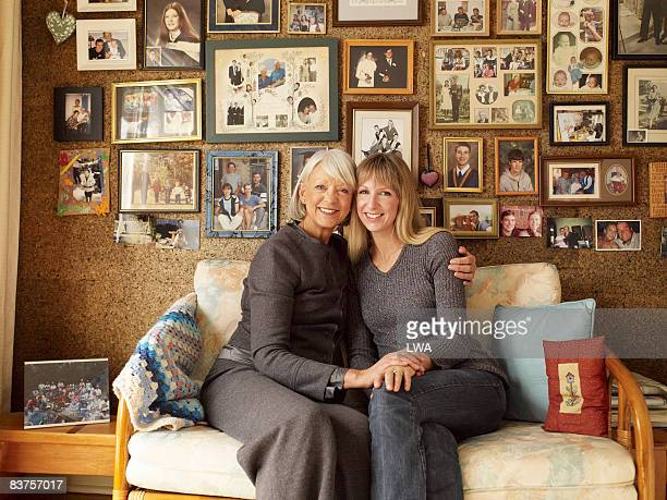 Mother and Daughter By Wall of Family Pictures